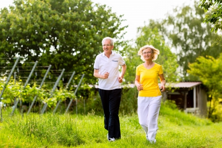 Senior Couple doing sport outdoors, jogging on a road or path in the nature photo