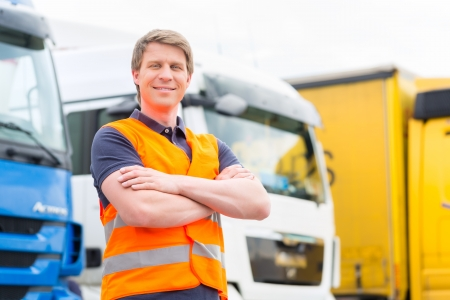delivery driver: Logistics - proud driver or forwarder in front of trucks and trailers, on a transshipment point