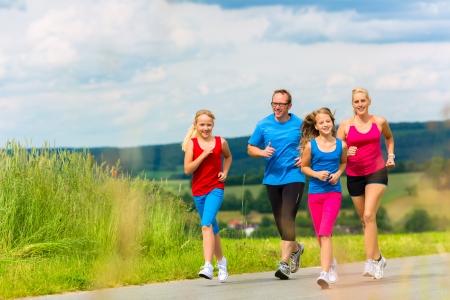 가벼운 흔들림: 가족 - 어머니, 아버지와 네 자녀 - 농촌 거리에 체력을 위해 조깅이나 야외 스포츠를 하