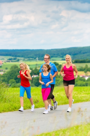Family - mother, father and four children - doing jogging or outdoor sport for fitness on rural street Stock Photo - 22042204