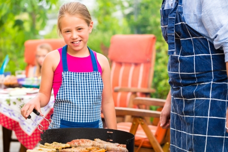 family garden: Father and daughter making barbecue in the garden in summer with sausages and meat