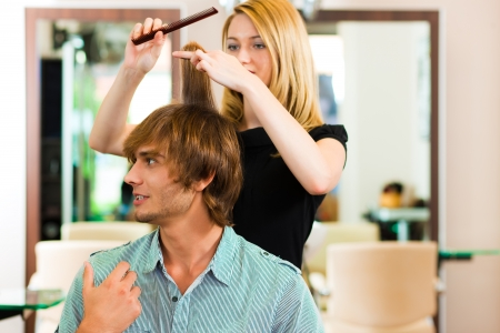 Man at the hairdresser, she is cutting his hair Stock Photo - 22087911