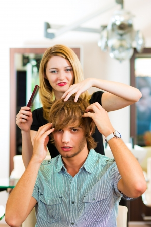 Man at the hairdresser, she is cutting his hair photo
