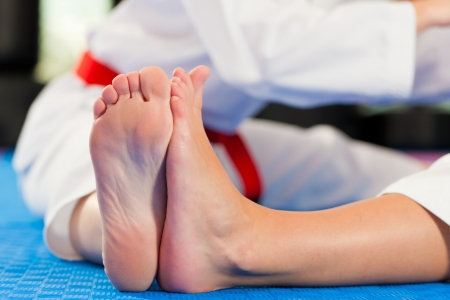 black belt: Woman in martial art training in a gym, she is stretching and warming up