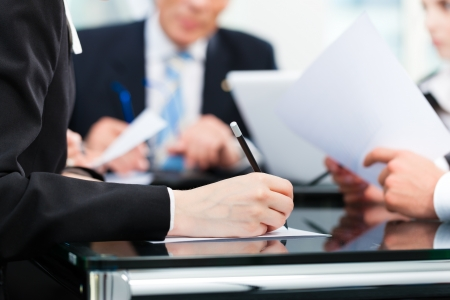 law: Business - meeting in an office, lawyers or attorneys discussing a document or contract agreement Stock Photo
