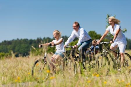 아기와 딸이 아름다운 풍경에 여름 날에 그들의 자전거에 주말 여행을 갖는 가족 스톡 콘텐츠