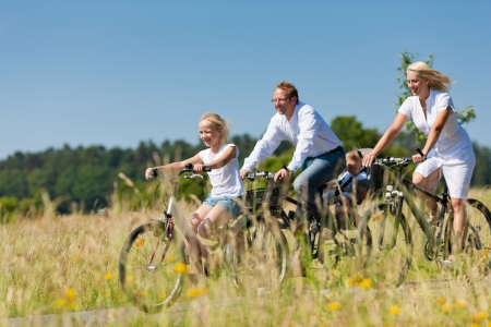 Gezin met baby en en dochter die een weekend excursie op hun fietsen op een zomerse dag in het mooie landschap