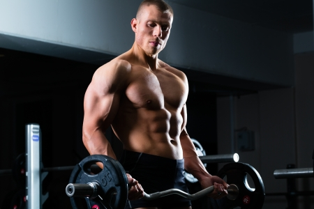 dumbells: Strong man - bodybuilder with dumbbells in a gym, exercising with a barbell Stock Photo