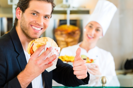 pinchos morunos: Doner kebab - vendedor amable y los clientes en un restaurante de comida rápida turca, con un pan de pita recién hecho o kebab en frente del pincho Foto de archivo