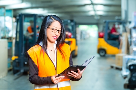 forwarding: Log�stica - trabajadora o supervisor con tablet PC en el almac�n de la empresa de transporte de carga