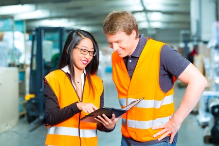 Logistics Teamwork - Worker or warehouseman and his female coworker with tablet computer at warehouse of freight forwarding company photo