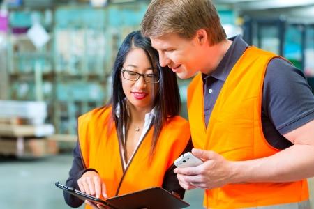 Logistik Teamwork - Worker oder Lagerarbeiter und seine weiblichen Mitarbeiter mit Tablet-Computer im Warenlager der Spedition