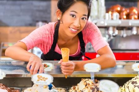 Jonge Aziatische verkoopster in een ijssalon neemt een bolletje ijs