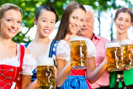 In Beer garden - friends, man and women in Tracht, Dirndl and Lederhosen drinking a fresh beer in Bavaria, Germany Stock Photo - 22088011