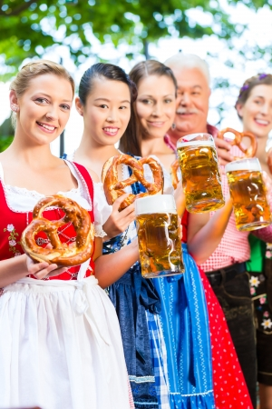In Beer garden - friends, man and women in Tracht, Dirndl and Lederhosen drinking a fresh beer in Bavaria, Germany Stock Photo - 22088023