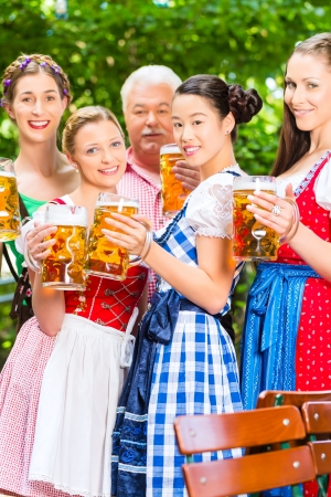 In Beer garden - friends, man and women in Tracht, Dirndl and Lederhosen drinking a fresh beer in Bavaria, Germany Stock Photo - 22088024