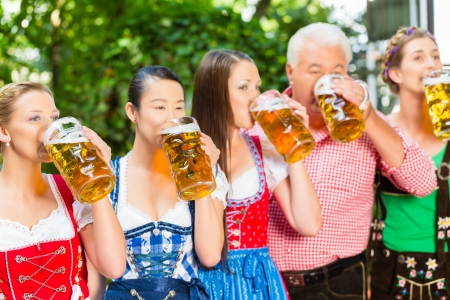 In Beer garden - friends, man and women in Tracht, Dirndl and Lederhosen drinking a fresh beer in Bavaria, Germany Stock Photo - 22088025