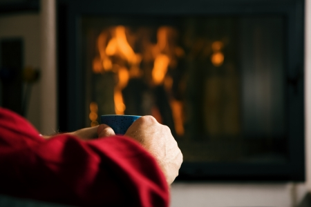 Mature man  only hands to be seen  drinking a glass of mulled wine in front of his fireplace in the comfort of his home Stock Photo - 23389901