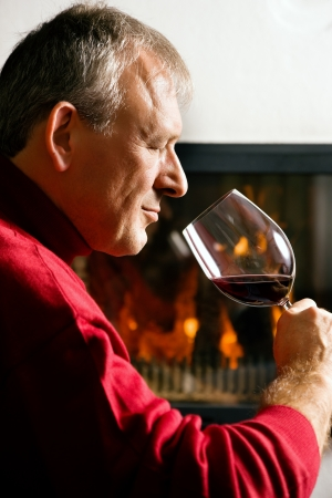 Mature man enjoying a glass of red wine in front of a fire Stock Photo - 23389903