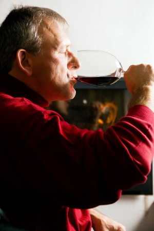 Mature man enjoying a glass of red wine in front of a fire Stock Photo - 23389904