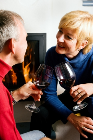 Mature couple having fun clinking glasses with red wine in a romantic setting Stock Photo - 23389908