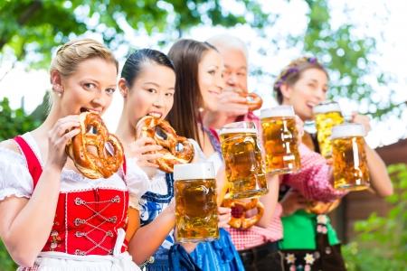 ビアガーデン - 友人、男性と女性の Tracht、ギャザー スカート ハーフパンツ ババリア、ドイツの新鮮なビールを飲む 写真素材