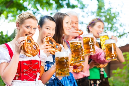 tracht: In Beer garden - friends, man and women in Tracht, Dirndl and Lederhosen drinking a fresh beer in Bavaria, Germany