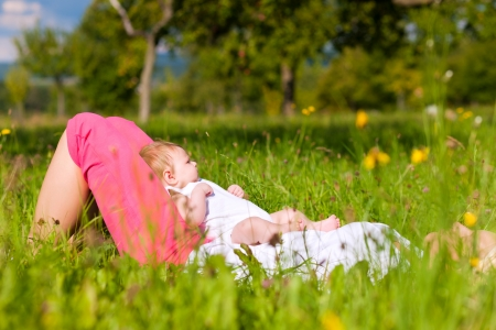 mom holding baby: Mother playing with her baby on a great sunny day in a meadow with lots of green grass and wild flowers