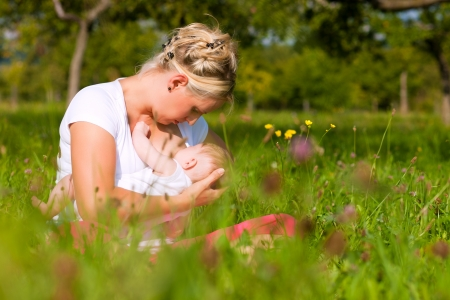 adult breastfeeding: Mother breastfeeding her baby on a great sunny day in a meadow with lots of green grass and wild flowers