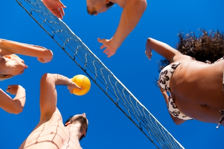 volleyball: Players doing summer sports trying to block a dangerous attack in a beach volleyball game Stock Photo