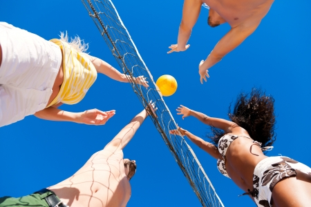 Players doing summer sports trying to block a dangerous attack in a beach volleyball game Stock Photo - 22109989