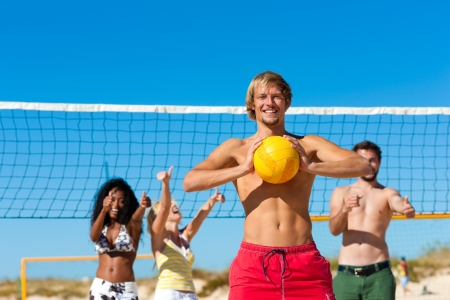 beach volleyball: Group of friends - women and men - playing beach volleyball, one in front having the ball Stock Photo