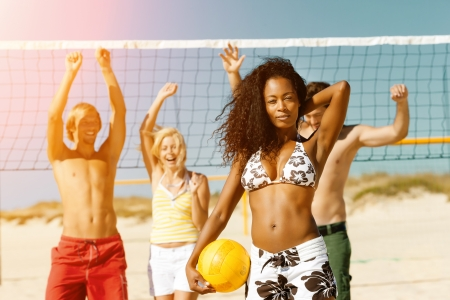 ballgame: Group of friends - women and men - playing beach volleyball, one in front having the ball Stock Photo