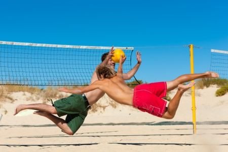 Group of friends  here two men to be seen - playing beach volleyball, they are jumping after the ball photo