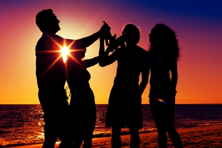 People (two couples) on the beach having a party, drinking and having a lot of fun in the sunset (only silhouette of people to be seen, people having bottles in their hands with the sun shining through) Stock Photo - 22110017