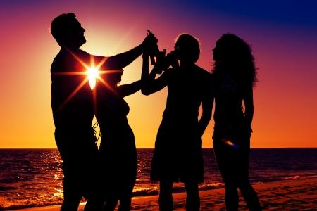 People (zwei Paare) am Strand eine Party, zu trinken und mit viel Spa? in den Sonnenuntergang (nur Silhouette von Menschen zu sehen, die Menschen mit Flaschen in der Hand mit der Sonne durch)