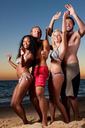 resor: Människor (två par) på stranden med en fest, dricka och ha mycket roligt i solnedgången (personer med flaskor i sina händer) Stockfoto