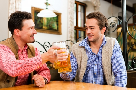 Two friends in Bavarian pub in traditional clothes sitting on their regular table in a pub Stock Photo - 23389920