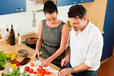 Man and woman in the kitchen - they preparing the vegetables and salad for dinner or lunch photo