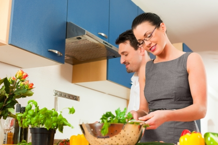 cutting vegetables: Man and woman in the kitchen - they preparing the vegetables and salad for dinner or lunch