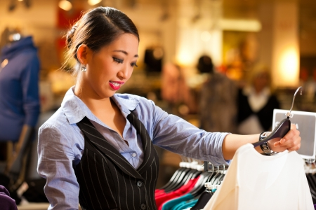 asian girl shopping: Woman of Asian - Chinese - origin in a shopping mall downtown looking for clothes