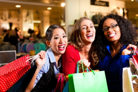 Group of three women - Caucasian, Latina and Asian - shopping downtown in a mall photo