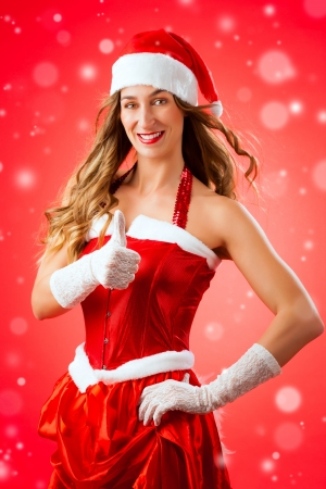 Attractive young woman in Santa Claus costume with thumbs up okay approval snow flakes on isolated red background Xmas celebration festive winter smiling happy photo