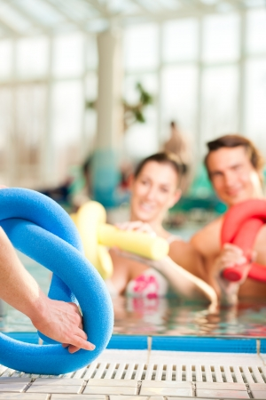 Fitness - a young couple - man and woman - doing sports and gymnastics or water aerobics under water in swimming pool or spa with swim noodle photo
