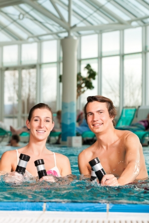 Fitness - a young couple - man and woman - doing sports and gymnastics or water aerobics under water in swimming pool or spa with dumbbells photo