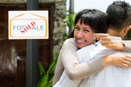 apartment market: Mercado de Bienes Ra�ces - joven pareja de Indonesia en busca de apartamento de bienes ra�ces o casa para alquilar o comprar, la mujer con las llaves