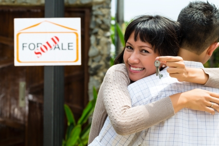home keys: Real estate market - young Indonesian couple looking for real estate apartment or house to rent or buy, the woman holding the keys Stock Photo