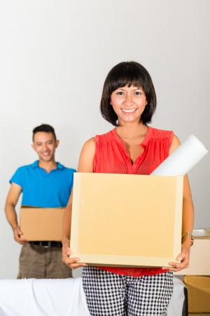 tenant: Real estate market - Young Indonesian couple moving in a home or apartment, they unpacking moving boxes
