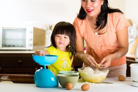 dadã  daughter: Indonesia asiática Niña y su madre en la cocina hornear un pastel juntos Foto de archivo