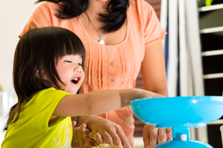 Indonesian Asian Little girl and her mother in the kitchen bake a cake together photo